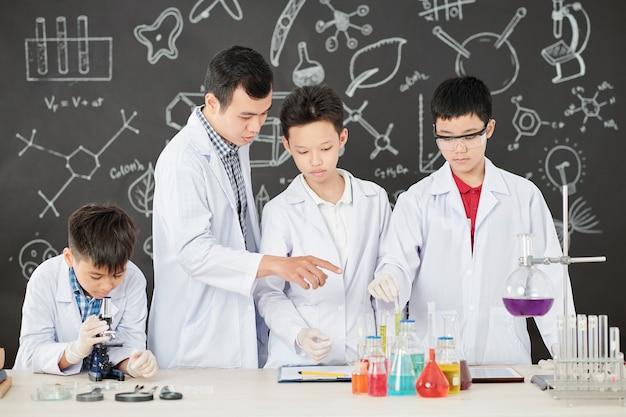 Profesor explicando la reacción química a los estudiantes cuando el niño de la escuela mirando la placa de petri a través del microscopio