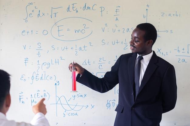 Profesor extranjero africano enseñando ciencias en el aula.