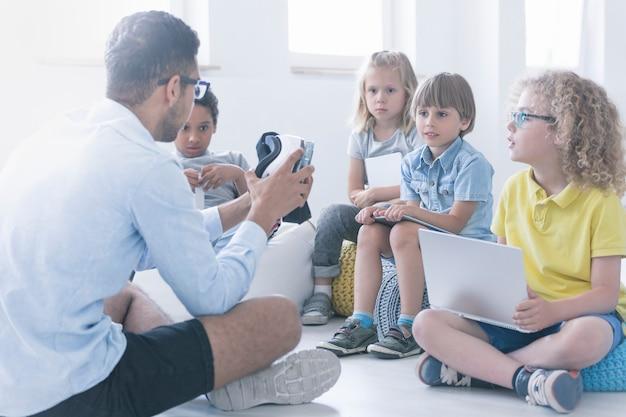 Profesor feliz muestra a los niños cómo funciona el robot durante la lección de robótica