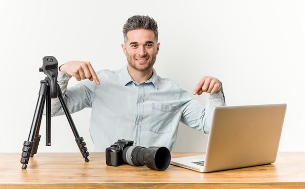 Profesor de fotografía guapo joven apunta hacia abajo con los dedos, sentimiento positivo.