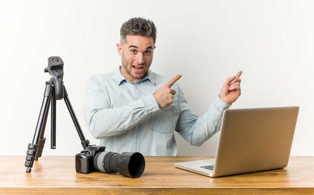 Profesor de fotografía guapo joven apuntando con el dedo índice a un espacio de copia, expresando emoción y deseo.