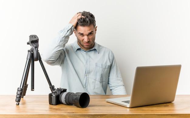Profesor de fotografía guapo joven cansado y con mucho sueño manteniendo la mano en la cabeza.