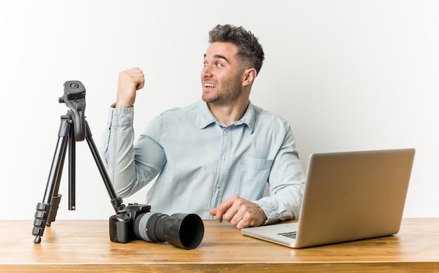 Profesor de fotografía guapo joven señala con el dedo pulgar, riendo y despreocupado.