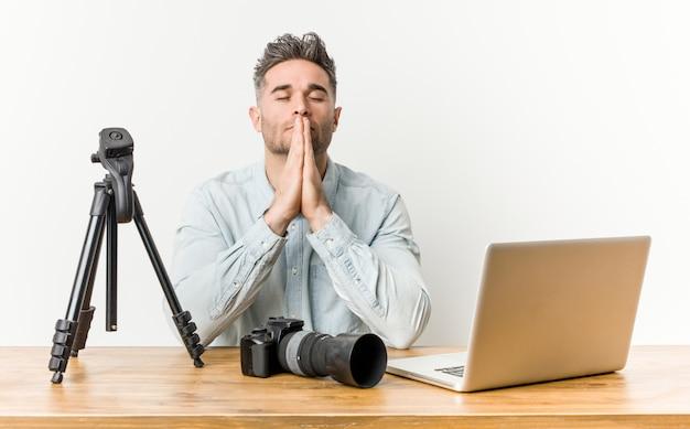Profesor de fotografía guapo joven tomados de la mano en rezar junto a la boca, se siente seguro.