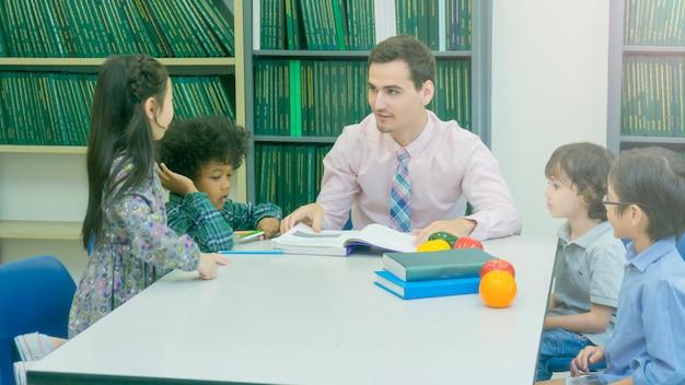 Profesor y grupo de estudiantes aprendiendo y hablando con el libro de colores con estantería