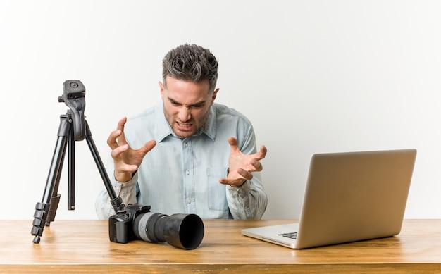 Profesor guapo joven de fotografía molesto gritando con las manos tensas.