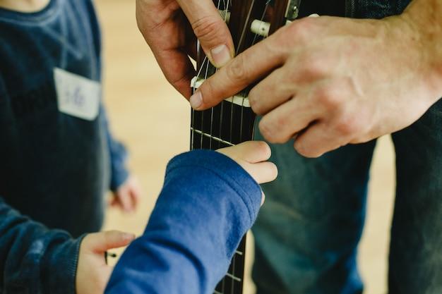 Profesor de guitarra que indica a un niño pequeño estudiante la colocación de los dedos en el mástil.