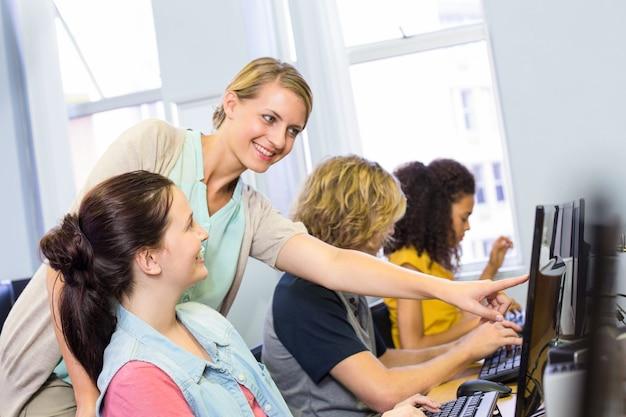 Profesor de informática ayudando a estudiantes mujeres