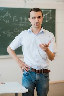 Profesor joven cerca de la pizarra en el aula de la escuela hablando con la clase