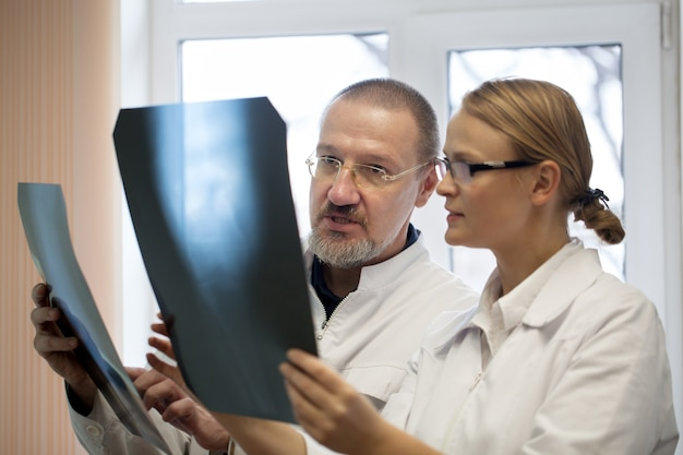Profesor y joven médico que compara radiografías