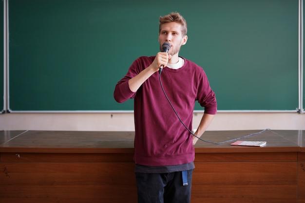 Profesor joven profesor hablando con el micrófono en la sala de conferencias de pie cerca de la pizarra