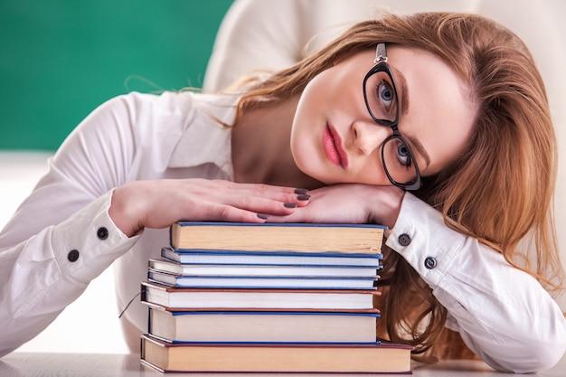 Profesor con libros en el aula.