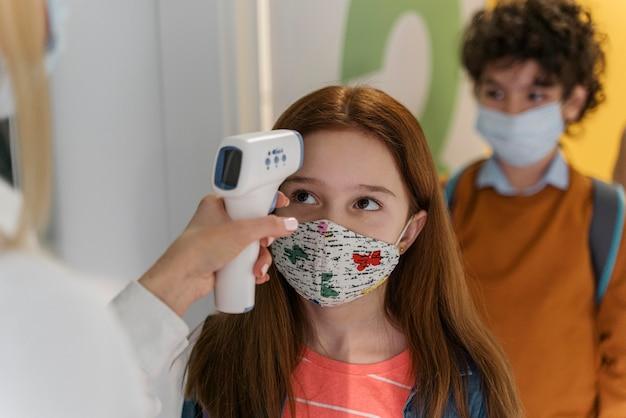 Profesor con máscara médica comprobando la temperatura de los niños en la escuela