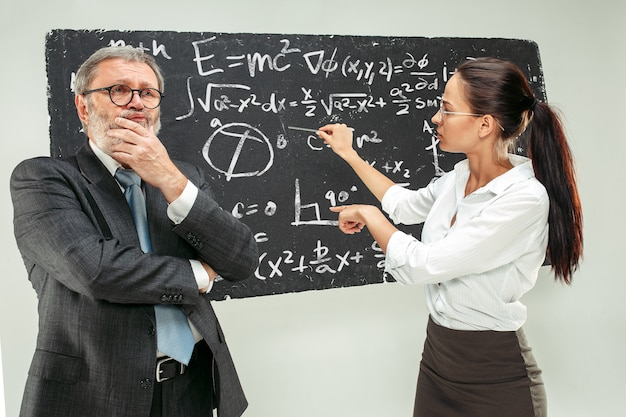 Profesor masculino y joven contra la pizarra en el aula