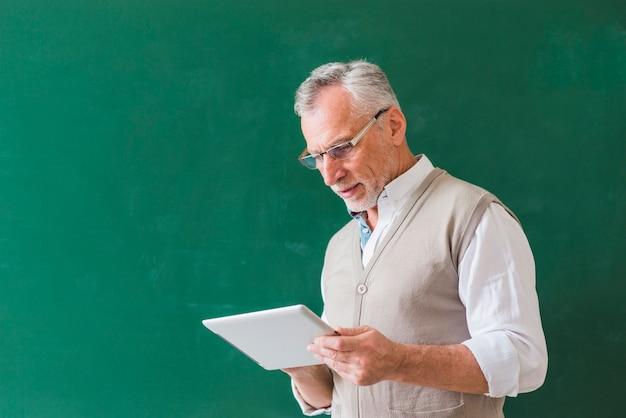 Profesor masculino mayor que usa la tableta cerca de la pizarra
