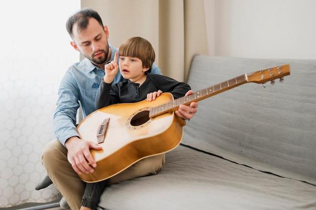 Profesor masculino tutoría a un niño en casa para clases de guitarra