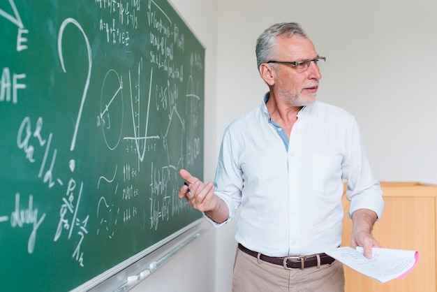 Profesor de matemáticas de edad avanzada que explica la fórmula en el aula
