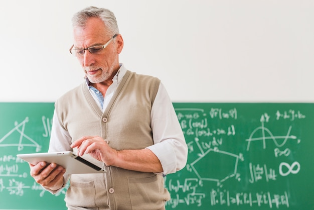 Profesor de matemáticas envejecido concentrado que calcula en la tableta