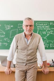 Profesor mayor alegre que se coloca cerca del escritorio del profesor en sitio de conferencia