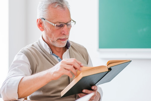 Profesor mayor leyendo un libro sentado en el aula