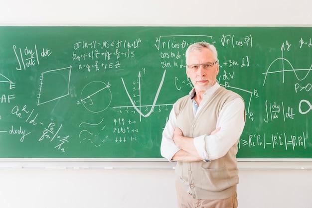 Profesor mayor de pie junto a la pizarra en el aula