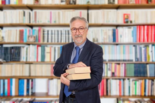 Profesor mayor que se coloca que sostiene un libro delante de un estante para libros