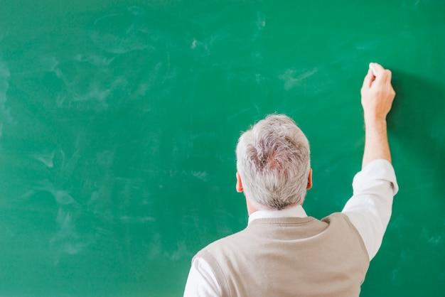 Profesor mayor que escribe en el tablero verde con tiza
