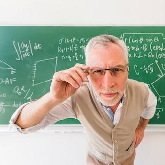 Profesor mayor que mira a través de los vidrios en la cámara
