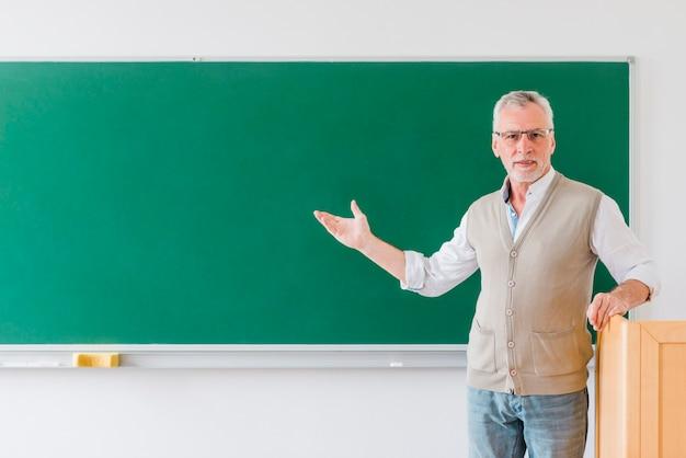 Profesor mayor que señala en la pizarra