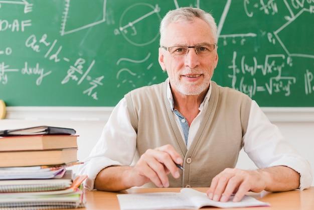 Profesor mayor que se sienta en el escritorio en sala de conferencias