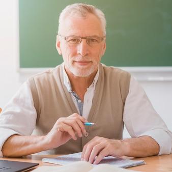 Profesor mayor que sostiene la pluma en el lugar de trabajo en sala de clase