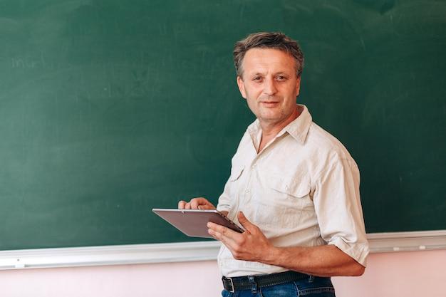 Profesor de mediana edad al lado de la pizarra con un ipad y explica una lección.