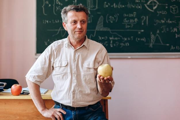 Profesor de mediana edad con una manzana en la mano y sonriendo mirando.