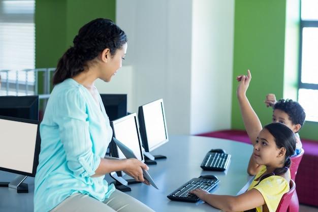 Profesor mirando a los niños levantando las manos