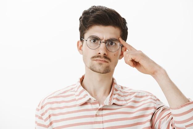 Profesor molesto molesto pidiendo pensar con el cerebro. hombre serio disgustado con barba y bigote en gafas de moda, sosteniendo el dedo índice en la sien y regañando al estudiante sobre una pared gris