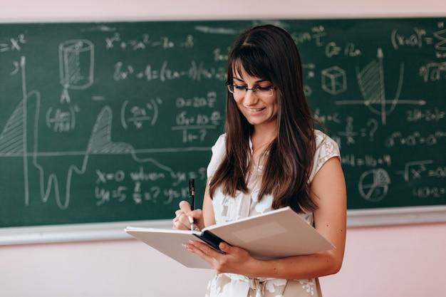 Profesor de la mujer que sostiene un libro de estudio y que escribe en él.