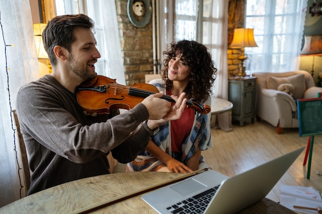 Profesor de música masculino privado dando lecciones de violín a una mujer en casa