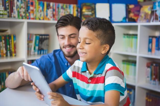 Profesor y niño de escuela con mesa digital en biblioteca