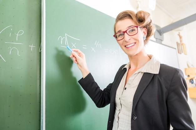 Profesor o docente escribiendo con tiza en la pizarra o pizarra o pizarra mientras la lección de matemáticas en la clase de la escuela