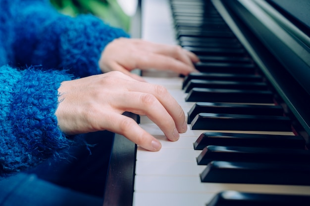 Profesor pianista músico ensayando música clásica. músico profesional estilos de vida en interiores. mujer irreconocible tocando el piano. detalle de las manos femeninas que tocan un teclado en casa.