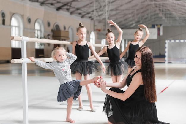 Profesor con pie de principiante en la mano en la clase de baile