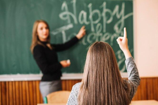Profesor preguntando al alumno levanta su mano