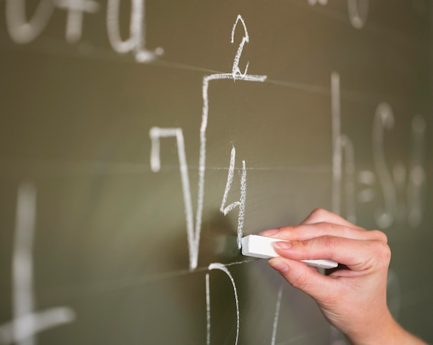Profesor de primer plano escribiendo en la pizarra