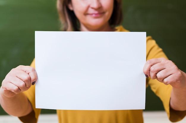 Profesor de primer plano sosteniendo la hoja de papel en blanco