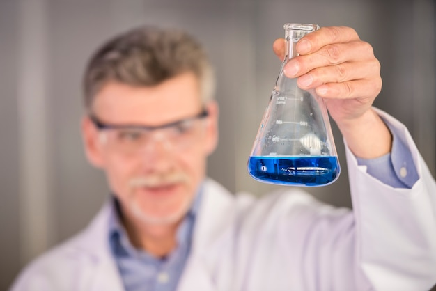 Profesor de química senior sosteniendo frasco con líquido azul.