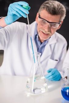 Profesor de química senior trabajando en laboratorio.