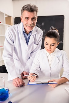 Profesor de química y su asistente trabajando en laboratorio.