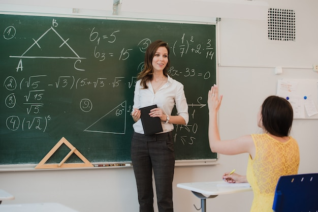 Profesor respondiendo la pregunta de los alumnos en el aula