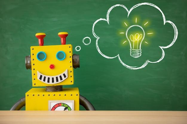 Profesor de robot de juguete divertido contra la pizarra con espacio de copia en clase.