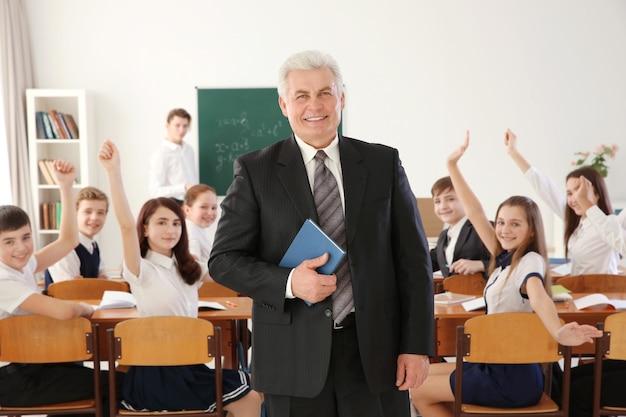 Profesor senior con cuaderno y alumnos felices en superficie